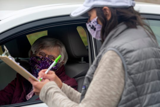 Michelle Litke records people who have picked up materials to make masks at the Scottish Rite Center in Salem on April 24, 2020. Members of the Mid-Valley Quilt Guild meet to pick up kits, drop off masks every Tuesday and Friday.
