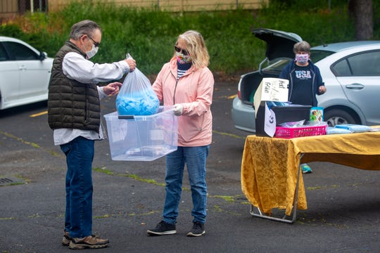 Will Satak drops off masks he sewed with his wife Reenie, to Tami Llewellyn at the Scottish Rite Center in Salem on April 24, 2020. Members of the Mid-Valley Quilt Guild meet to pick up kits, drop off masks every Tuesday and Friday