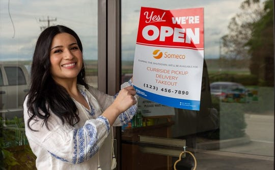 Myriam Vasquez, the e-commerce manager with Casey Printing, shows an example of a free sign that the King City business is offering to print for free amid the COVID-19 pandemic.
