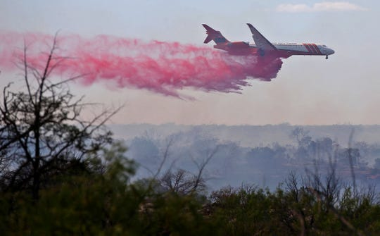 An aircraft drops fire retardant on the Holcombe Road Fire burning approximately 35 miles southwest of Ozona in West Texas on Thursday, April 23, 2020.