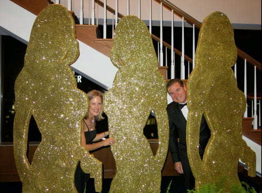 "Michele and Quintin Hardtner peek out from glittery Bond-Girl cutouts at Opera  007 Gala. The photo illustrates a way a photographer can set up  an unusual ""posed"" picture."
