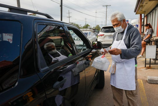 Sontaya Netthongkuma, house manager at Thai Express, delivers an order to a customers car on Friday, April 24, 2020.