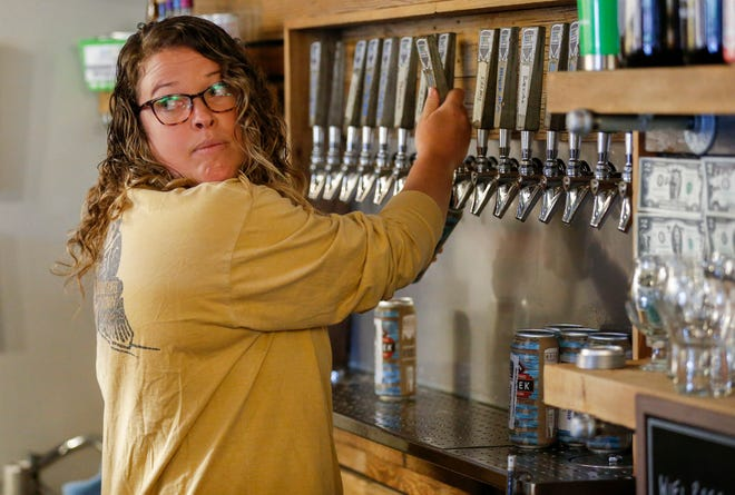 Alaina Williams fills cans of beer for curbside pick-up at 4 By 4 Brewing Company on Friday, April 24, 2020.