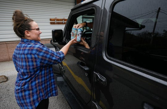 Allicyn Hollis delivers beer to a customer's car at 4 By 4 Brewing Company on Friday, April 24, 2020.