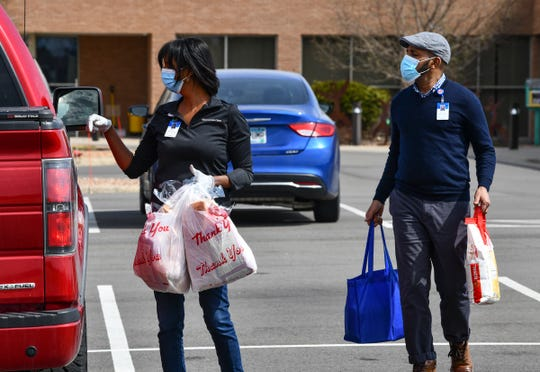 Hani Jacobson and Kahin Adam deliver food to families waiting in their cars during a food distribution drive Thursday, April 23, 2020, in St. Cloud.