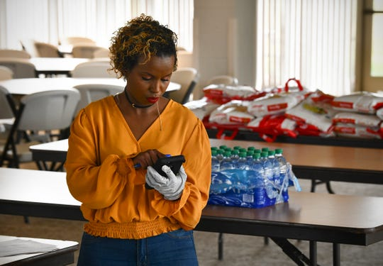 Mahado Ali works the phones during a food distribution drive Thursday, April 23, 2020, in St. Cloud.