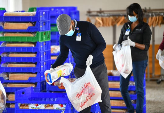 Kahin Adam and Hani Jacobson package food into bags during a distribution drive Thursday, April 23, 2020, in St. Cloud.