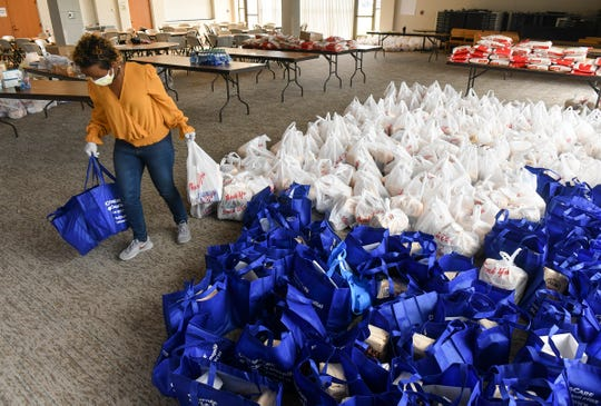 Mahado Ali collects items for distribution during a food drive Thursday, April 23, 2020, in St. Cloud.