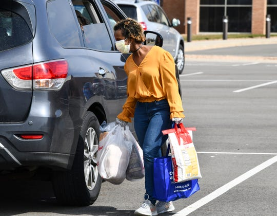 Trauma-informed care specialist Mahado Ali delivers food during a food distribution drive Thursday, April 23, 2020, in St. Cloud.