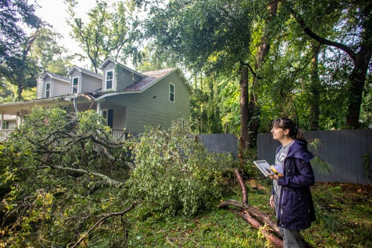 Jennifer Drury surveys the damage caused by the thunderstorms that passed through Tallahassee Thursday evening. A large branch fell from a tree and clipped the front corner of her porch.