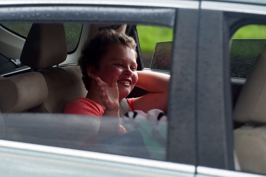 Melodie Caudle, a 5th-grader at Beachland Elementary School in Vero Beach, waves to friends, classmates and community members welcoming her home on Friday, April 24, 2020, as she is escorted around the Indian River Mall by local law enforcement agencies. Caudle was diagnosed with acute promyelocytic leukemia in August 2019 and received her final chemotherapy treatment on Friday. Caudle was being treated at the Nemours Children's Hospital in Orlando.