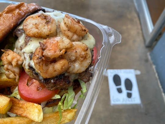 """A surf 'n' turf burger """"to go"""" is seen with a 6-foot spacing marker near the front door at Chef David's Kitchen and Catering in Santa Paula."""