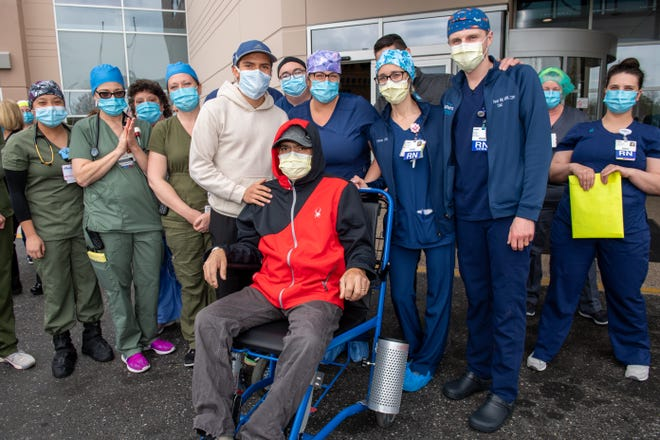 Staff members from Inspira Medical Center Vineland join Miguel Veragallardo, 50, of Cedarville and his son, Miguel (standing to his father's left), as he is discharged after a month-long battle against COVID-19.