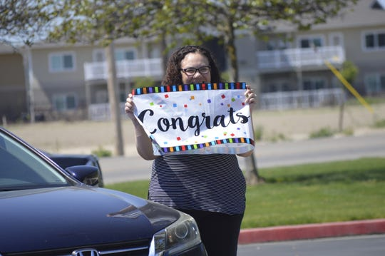 Yvonne Pena, a Mission Oak High School soccer mom, holds up a 'Congrats' sign on Friday during Hawks' soccer player Isaiah Borjon's signing day ceremony.