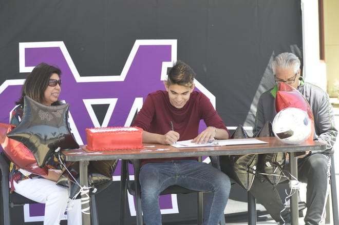 Mission Oak High School senior Isaiah Borjon signs his letter of intent to play college soccer at Gardner Webb University in front of his mother, Eliza, and father, Dave, on Friday in Tulare.