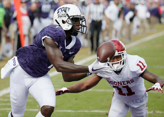 FILE - In this Oct. 20, 2018, file photo, TCU wide receiver Jalen Reagor (1) catches a pass in the end zone for a touchdown as Oklahoma cornerback Parnell Motley (11) defends during the first half of an NCAA college football game in Fort Worth, Texas. Reagor is a possible pick in the NFL Draft which runs Thursday, April 23, 2020, thru Saturday, April 25. (AP Photo/Brandon Wade, File)