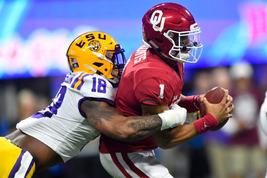FILE - In this Dec. 28, 2019, file photo, LSU linebacker K'Lavon Chaisson (18) sacks Oklahoma quarterback Jalen Hurts (1) during the first half of the Peach Bowl NCAA semifinal college football playoff game in Atlanta. Chaisson is a possible pick at the NFL Draft which runs Thursday, April 23, 2020, thru Saturday, April 25. (AP Photo/John Amis, File)