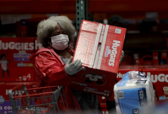 A customer in a protective mask picks up a box of Huggies diapers at a Costco store in Novato, Calif. Americans began stocking up on diapers after the World Health Organization declared the coronavirus a pandemic.