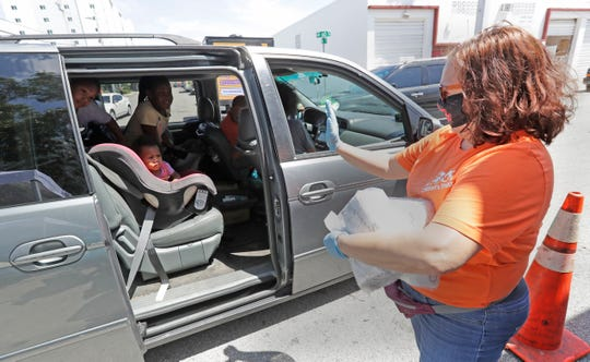Susan Marian, assistant to the CEO of the Children's Trust, helps distribute diapers at Curley's House of Style, a food bank in Miami. Curley's House of Style, along with the Children's Trust and the Miami Diaper Bank, distributed diapers and baby items to families financially hurt by the coronavirus pandemic.