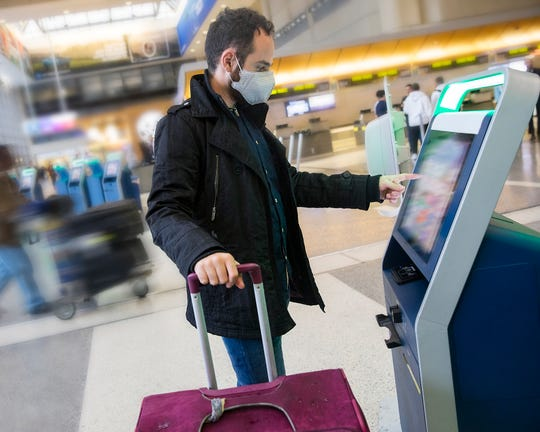 An airport traveler wears a face mask.