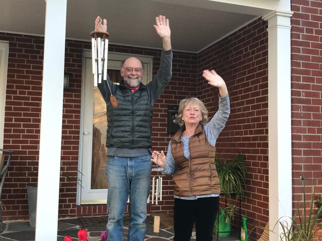 Jane Ridley and husband Bryan Humphrey shout,  wave and ring wind chimes on a Thursday to show support for healthcare workers during the ongoing coronavirus crisis.