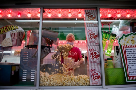 Deborah O'Connor fills popcorn boxes as Skelly's Amusements sells drive-thru carnival food Friday, April 24, 2020 in Williamstown, N.J.