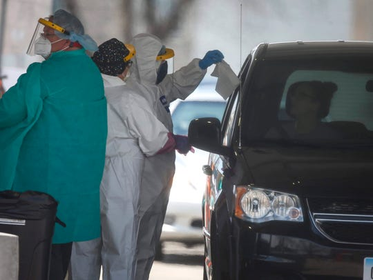 Medical staff administer COVID-19 tests to the public at the Iowa Events Center parking lot in Des Moines on Saturday, April 25, 2020. The tests were done by appointment only.