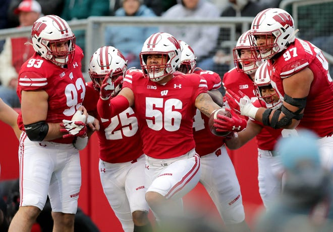 Zack Baun (56) and the Wisconsin defense celebrate after Baun returned an interception 34 yards for a touchdown against Michigan State in the fourth quarter Oct. 12, 2019.