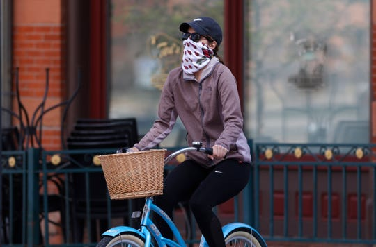 A bicyclist wears face protection against the new coronavirus while pedaling through Larimer Square early Saturday in downtown Denver.