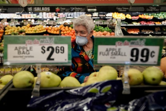 FILE - In this March 17, 2020 file photo, Carmen Zamora shops at Northgate Gonzalez Market in Santa Ana, Calif., during an early-hour shopping time for those over 65 and the disabled.