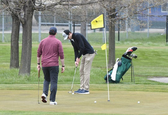 A golfer makes his shot at Chandler Park Golf Course Saturday in Detroit.