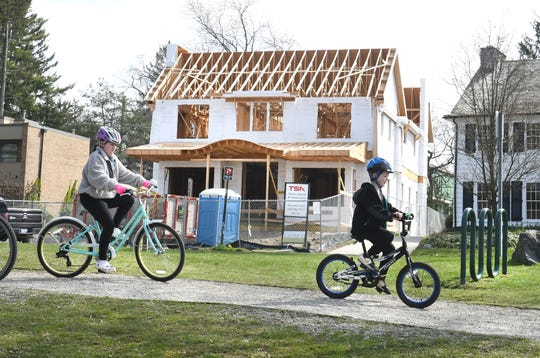 Bicycle riders pass the unfinished home at 660 Lakeside Drive in Birmingham as the owners are suing the city of Birmingham because they have not been able to finish the roof, windows and doors and they are concerned about weather damage.