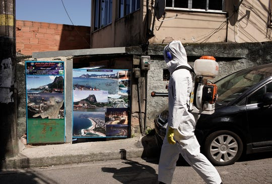 Water utility workers from CEDAE disinfect in the Vidigal favela in an effort to curb the spread of the new coronavirus, in Rio de Janeiro, Brazil, Friday, April 24, 2020.