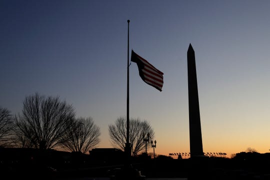 FILE - In this Thursday, Dec. 19, 2019 file photo, a flag at the World War II Memorial flies upside down after it unclipped from its snaphook, before sunrise on Capitol Hill in Washington. At right is the Washington Monument.