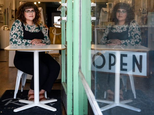 Heather Vaught, owner of River City Coffee + Goods, sits at the door of the shop's Main Street storefront in Downtown Evansville, Ind., Saturday morning, April 25, 2020. The business is currently only open for curbside pick-up or local porch deliveries on Wednesdays and Saturdays from 10 a.m. to noon due to restrictions from the COVID-19 pandemic.