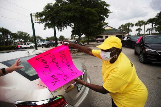 Gwynetta Gittens attaches census signs to vehicles in Lehigh Acres. A group of residents went out to encourage residents to participate in the 2020 count.