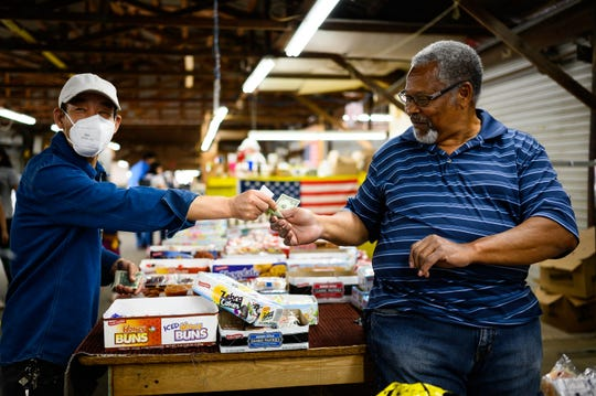 Wesley Lee, left, buys snacks from Jerry Walton at the Anderson Jockey Lot Saturday, April 25, 2020.
