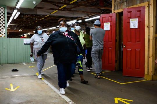 Shoppers walk through the indoor vendor area at the Anderson Jockey Lot Saturday, April 25, 2020.