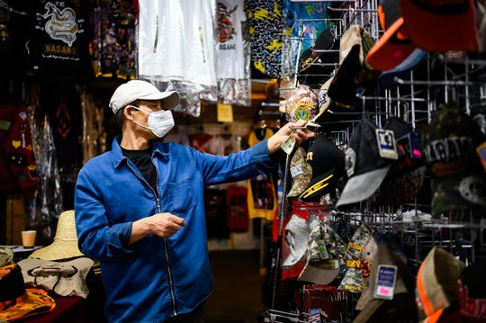 Wesley Lee searches for a hat for a customer at the Anderson Jockey Lot Saturday, April 25, 2020.