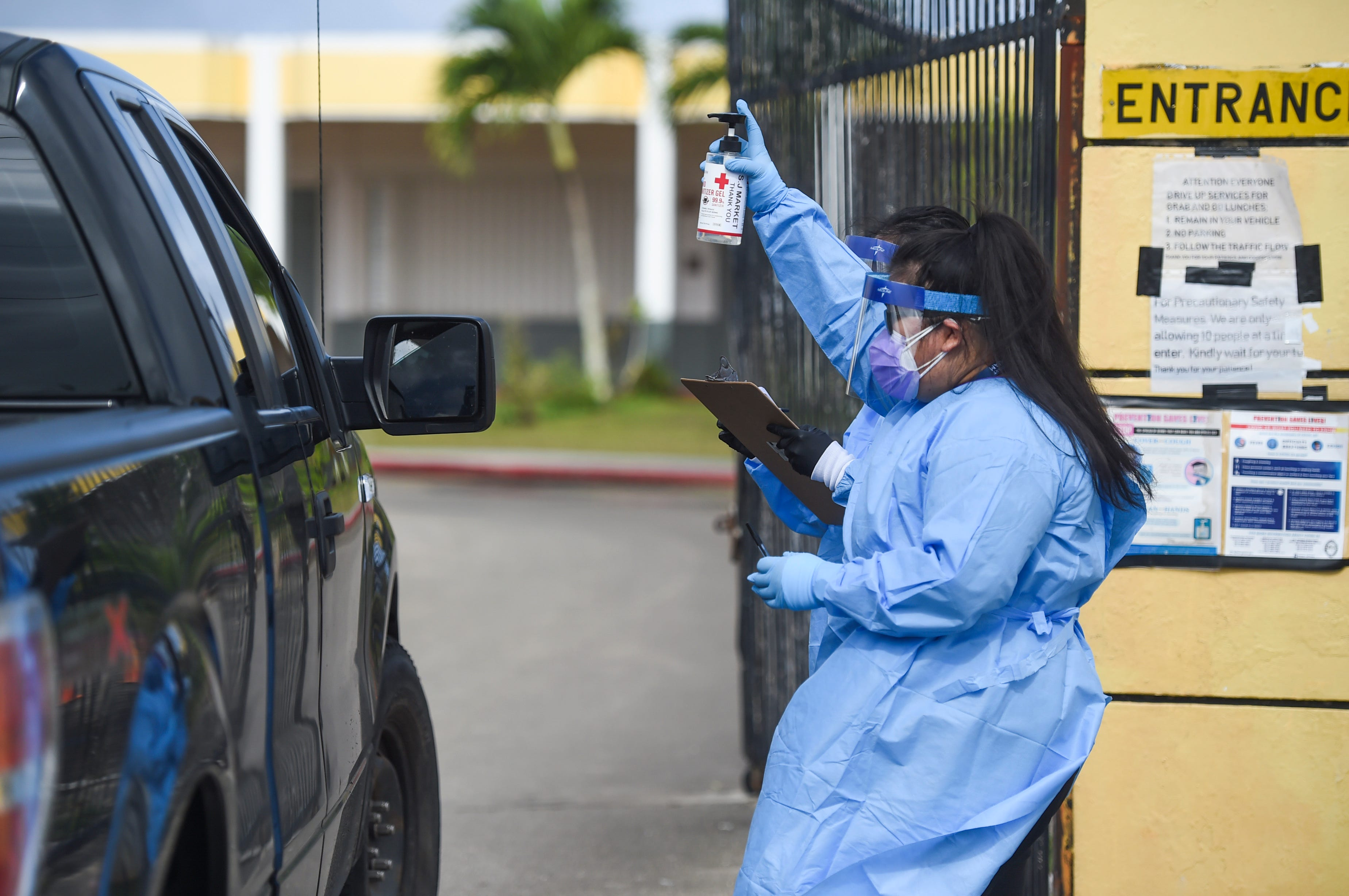 A nurse from the Department of Public Health and Social Services offers hand sanitizer gel to a drive-up patient during the government's COVID-19 testing pilot program at Astumbo Gym in Dededo in this April 25 file photo.