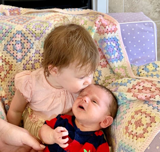 18-month-old  Hannah gives newborn Gordon a kiss.