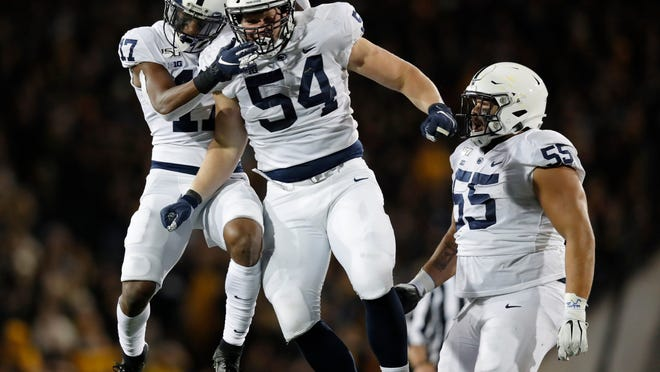 Penn State defensive tackle Robert Windsor, center, celebrates a sack with safety Garrett Taylor, left, and defensive tackle Antonio Shelton, right, during the second half of an NCAA college football game against Iowa, Saturday, Oct. 12, 2019, in Iowa City, Iowa. (AP Photo/Matthew Putney)