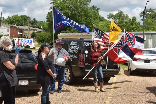 'Open up Mississippi' rally participants listen to instructions given by rally organizers at the Mississippi Farmers Market on High Street in Jackson. The demonstrators drove around the Governor's Mansion multiple times, honking and cheering on Saturday, April 25, 2020.