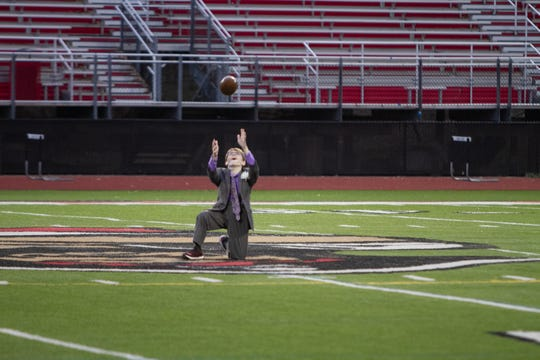 Pinckney High School senior Larry Prout Jr. tosses a game ball given to him Sept. 23, 2016 after his 100th surgery. Prout has spina bifida. He took a position in the center of the field as the stadium lights were turned on at approximately 8:20 p.m. Friday, April 24, 2020, or 20:20 in military time, to commemorate the Class of 2020 whose senior year was cut short due to the COVID-19 pandemic.