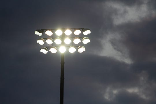 A bank of lights, one of four surrounding the Pinckney High School football stadium, comes on at approximately 8:20 p.m., expressed as 20:20 in military time, Friday, April 24, 2020. Numerous schools commemorated the 2020 class with this ceremony.