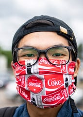 Brandon Lau poses wearing a handmade face mask in a parking lot in Memphis, Tenn., last month.