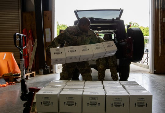 Alabama National Guard Sgt. Patris Bivens, 135th Expeditionary Sustainment Command (ESC), loads COVID 19 test kits for transport at the Alabama Department of Public Health Warehouse in Montgomery, Alabama, April 22, 2020.