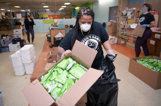 Gideon's Army trauma coordinator and case manager Deirdre Nicole Childress helps organize food and supplies at the resource center in Nashville on Saturday, April 25, 2020.