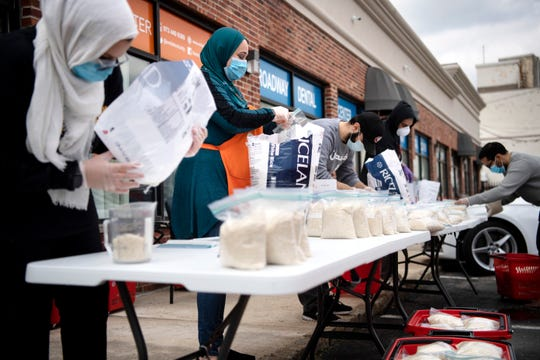 (Center) Melinda Abedrabbo and others package rice outside of SMILE for Charity in Passaic on Saturday, April 25, 2020. A coalition of Muslim-led nonprofits comprised of SMILE for Charity, FaithNYC, The Muslim Network, Islamic Center for Passaic County (ICPC), and others, package and deliver groceries weekly to hundreds of needy families in New Jersey and New York throughout the month of Ramadan amid the COVID-19 pandemic.