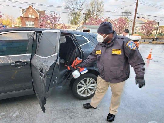 Sheriff Anthony Cureton sanitizing a vehicle